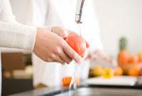 トマトを洗う女性の手元