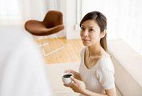 コーヒーカップを持って見上げる女性