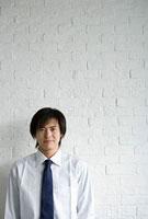 白いレンガの壁際に立つ男性