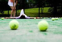 テニスコートで仰向けになる男性