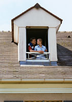 Couple standing at dormer window