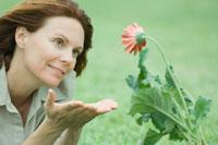 Woman beholding flower 11001036848| 写真素材・ストックフォト・画像・イラスト素材|アマナイメージズ