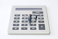 Miniature businessmen standing on calculator