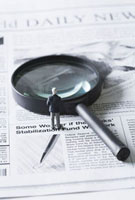 Miniature businessman standing before magnifying glass