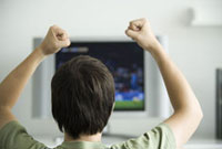 Male watching television,fists raised in air,rear view