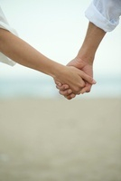 Couple holding hands outdoors, cropped