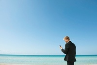 Young business man looking at cell phone by ocean