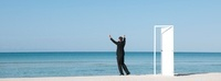 Businessman standing on beach looking at ocean with arms rai