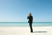 Businessman talking on cell phone while standing on beach, r