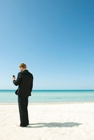 Young businessman using cell phone while standing on beach