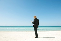 Businessman using cell phone on beach