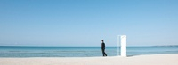 Businessman standing on beach next to half-open door, lookin