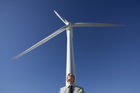 Businessman leaning against wind turbine