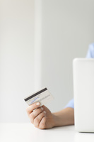 Woman holding credit card while using laptop computer, cropp