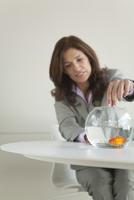Businesswoman feeding goldfish