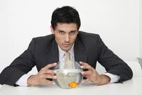 Businessman holding fishbowl with goldfish 11001056094| 写真素材・ストックフォト・画像・イラスト素材|アマナイメージズ