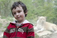 Boy in front of lion exhibit at zoo, portrait