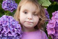 Little girl surrounded by hydrangea flowers, portrait