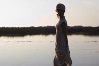 Young woman wearing dress in front of lake at dusk