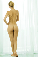 Nude woman standing by curtained window, rear view