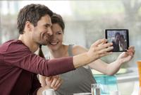 Couple smiling for selfie taken with digital tablet
