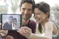 Couple using digital tablet to take a selfie