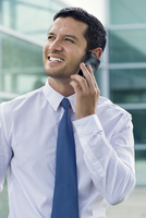 Businessman using cell phone, smiling