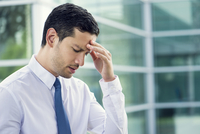 Businessman holding head and looking down in disappointment