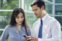 Businessman showing smartphone to colleague