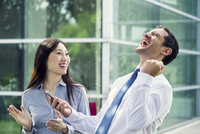 Businessman celebrating good news with colleague