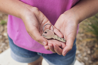 Girl holding key in cupped hands, cropped