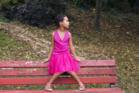 Girl sitting alone on park bench, looking away in thought