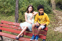 Girl and boy hanging out together on park bench