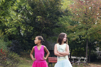 Girls standing together outdoors, both looking away angrily