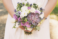 Bride holding bouquet of flowers and succulent plants, cropped
