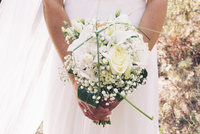 Bride holding bouquet of flowers, cropped