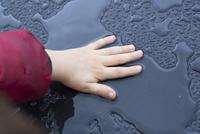 Child touching wet metallic surface