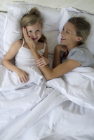 Mother and daugther lying in bed together