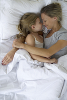 Mother and daughter in bed embracing