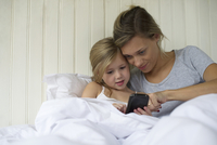 Mother and daughter using smartphone together