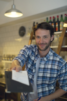 Shopkeeper presenting bill to customer
