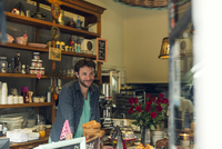 Shopkeeper behind counter at coffee shop
