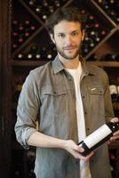 Wine salesman selecting bottle of wine