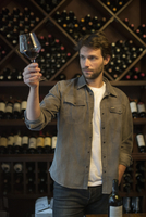 Wine connoisseur holding up glass of wine