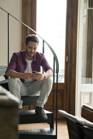 Man sitting on staircase using smartphone