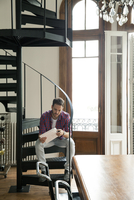 Man sitting on staircase opening package