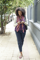 Woman text messaging while walking on sidewalk