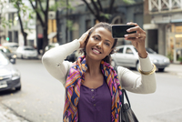 Woman taking selfie on street