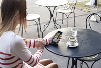 Young woman using multimedia smartphone in outdoor cafe