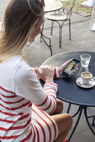 Young woman using multimedia smartphone at outdoor cafe
